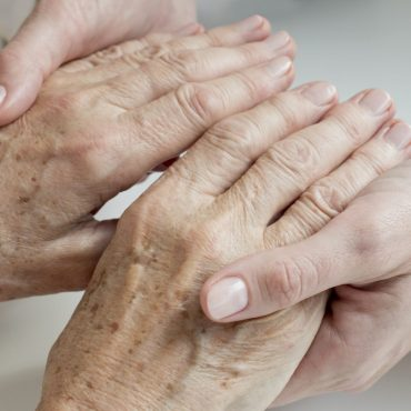 Female doctor examining senior patients hands